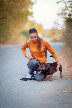 Young woman in orange turtleneck and jeans walks and hugs the dog