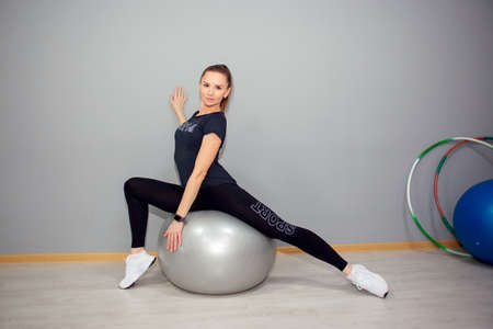 Beautiful young athletic woman posing while sitting on a big fitness ball Stok Fotoğraf