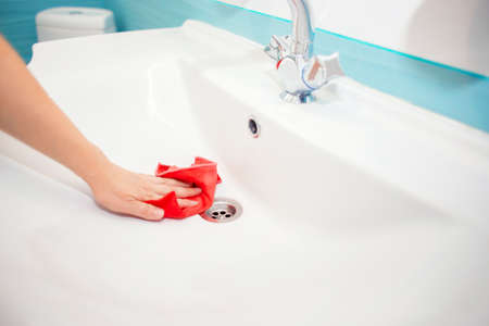 Washing the sink and faucet in the bathroom. Disinfection at home. Spring-cleaning. Cleaning the sink with a rag