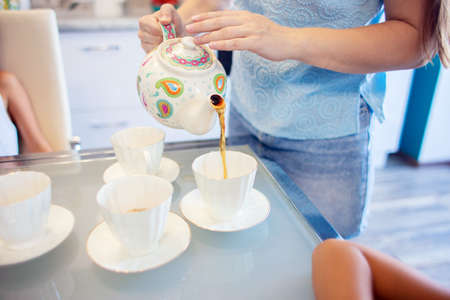 A woman pours tea from a teapot into cups. Preparing for tea in the kitchen