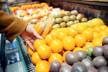 Woman chooses exotic fruits in the store. Granadilla on the counter of the store Stock fotó