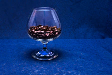 Fragrant roasted black coffee beans. Grains of coffee in a glass goblet. The sophistication of an old drink.
