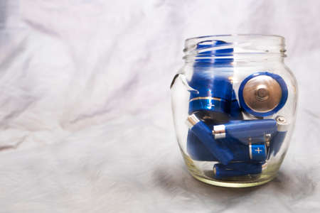 Batteries in a glass jar, symbol of energy conservation.