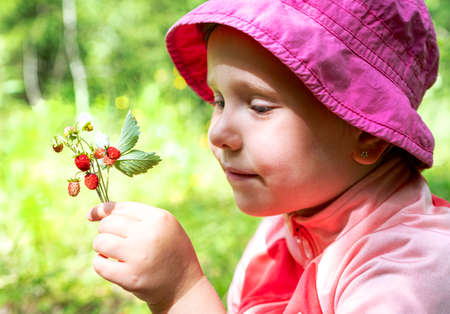 The child, a Caucasian girl, holds wild strawberries in his hand. The baby is smiling.