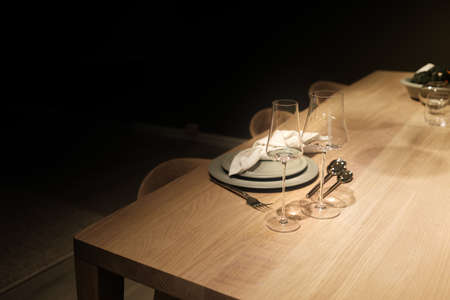 Low key photo of indoor restaurant with wine glasses on the wooden table with wooden chairs and green plate