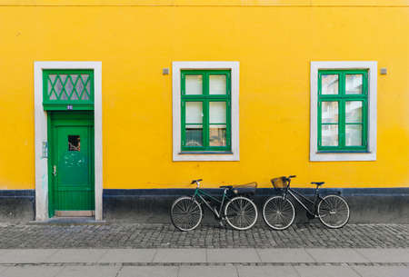 Copenhagen, Denmark - 08/19/2017: Bicycles set against the bold yellow wall and green wooden door and windows on the street