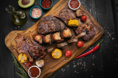 Assorted delicious grilled meat with vegetable and herbs on rustic table Archivio Fotografico
