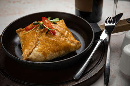 close-up of deep fried turnovers with a filling of minced beef and onion in a black ceramic pan on a white table Foto de archivo