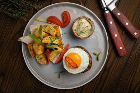 Beef medallions with egg, potatoes and peppers on a wooden background Foto de archivo