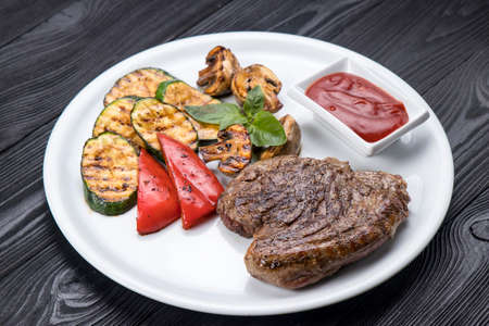 grilled steak, zucchini, on a white plate and black background
