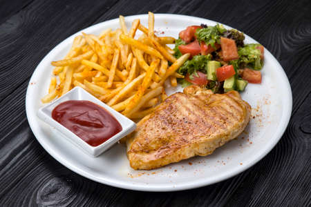 chicken, french fries, sauce on a white plate