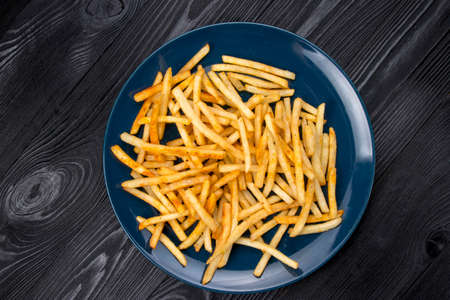 french fries on a blue plate and black background