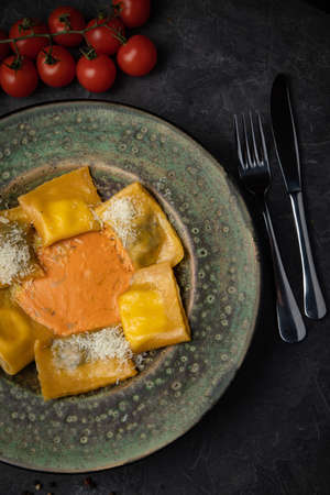 Yellow ravioli with cheese in a plate on a black background