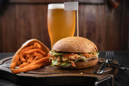 American hamburger with crab and french fries meat on wooden board