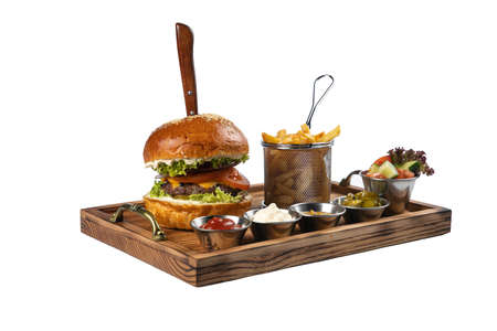 hamburger with cutlet, double cheese, sauces, salad and french fries on a white background