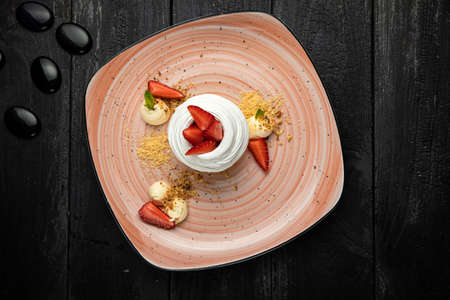 Homemade small strawberry pavlova meringue cakes with mascarpone cream and fresh mint leaves. Dish, dessert.