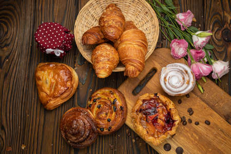 Assorted pastries, croissants, buns. On a brown wooden table. Archivio Fotografico