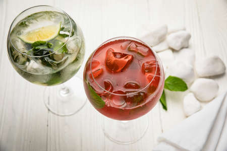 Assorted cold cocktails - mojito and raspberry. On a wooden, white table