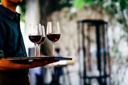 ウェイターは、赤のワイングラスを持つキャリング プレートです。 メガネ。 ワイングラス。 写真素材