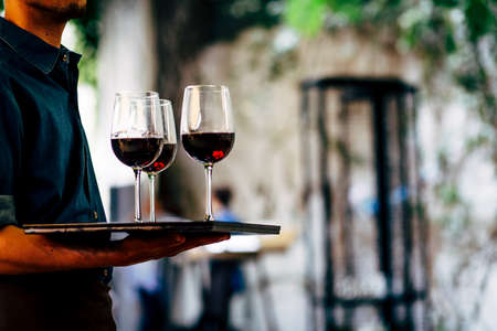 Waiter is carring plate with red Wine glasses.  glasses.  Wine glasses. Stock Photo
