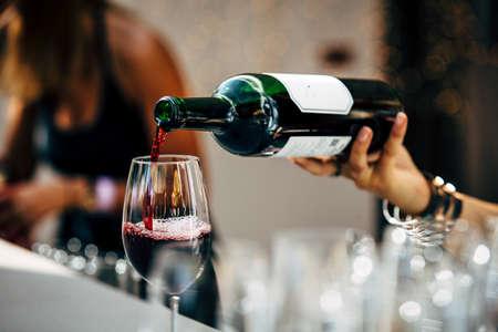 バーテンダーは、赤ワインを注ぐこと。 写真素材