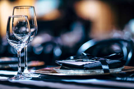 Luxury table settings for fine dining with and glassware, beautiful blurred  background. Preparation for holiday  Christmas and Hannukah dinner night.
