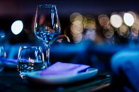 Luxury table settings for fine dining with and glassware, beautiful blurred  background. For events, weddings. Фото со стока