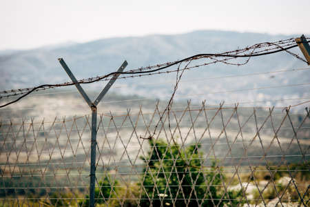 Razor wire fence in daylight view. International boarder between two countries.