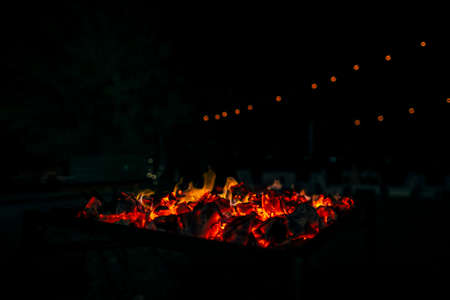 Night scene of fire sparks and flame burning with beautiful red flame.