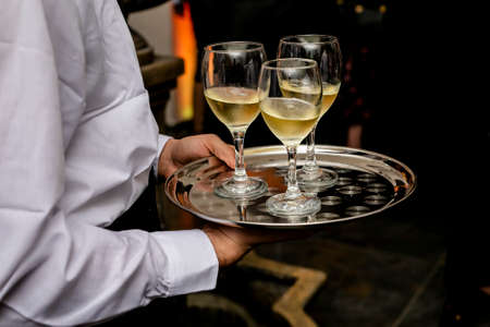 Waiter is holding a tray with white wine glasess. no face shown. white uniform.