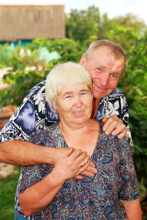 Smiling senior couple embracing outdoors photo