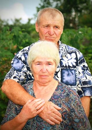 Sad senior couple embracing outdoors Standard-Bild