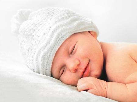 smiling european newborn baby in white hat Standard-Bild