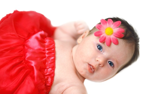 European newborn fashion baby girl with big blue eyes dressed in red lying down isolated on white