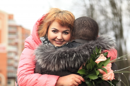 Happy young woman with flowers embracing man