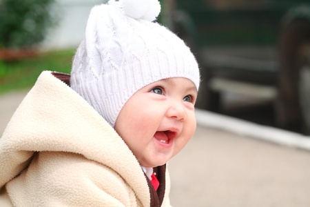 6 9 months: Smiling baby girl in white hat outside Stock Photo