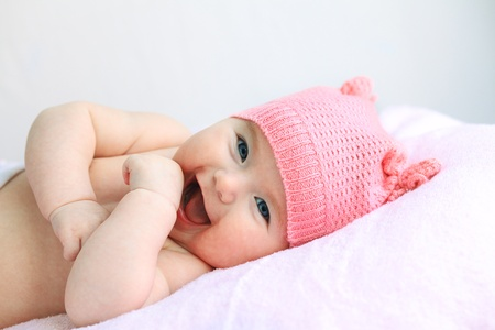 laughing european baby girl with big blue eyes in pink hat Stock Photo
