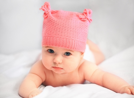 baby girl in pink hat looking at camera close up