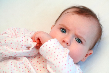 dreary: sad baby girl looking at camera close up Stock Photo