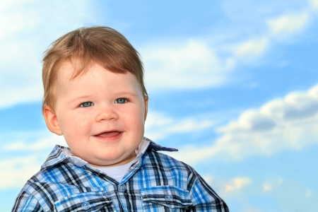 6 12 months: Smiling baby boy with blue eyes in sky