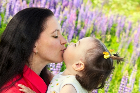 young mother kissing her little daughter