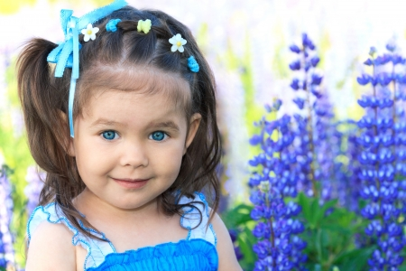 smiling little girl with big blue eyes in flowers