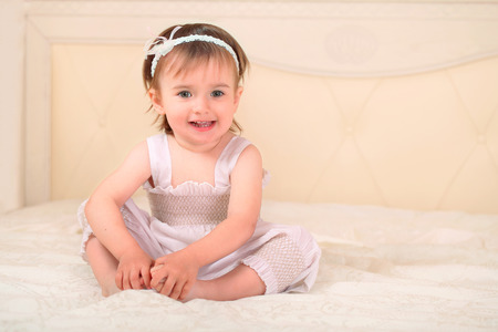cute baby girl sit in bed