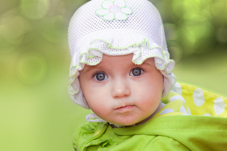 6 12 months: Funny baby girl looking in wide-eyed astonishment
