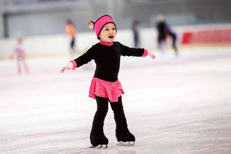 Piękna dziewczyna uczy się jeździć na łyżwach