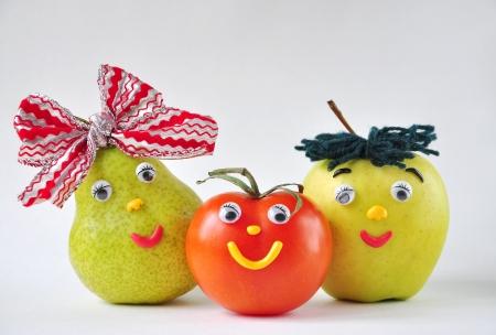 buena salud: Divertido tomate, manzana y pera en un fondo blanco Foto de archivo