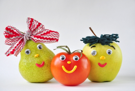 Funny tomato, apple and pear on a white background Фото со стока