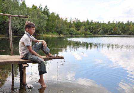 bambini tristi: ragazzo seduto su un ponte Archivio Fotografico
