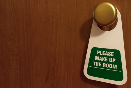 Signboard for hotel room which it`s hanging on a handle of door. photo