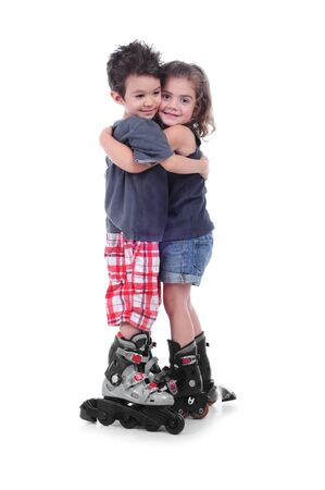 Cute boy and girl 4 years  with roller skating hug themself in a studio on white background photo